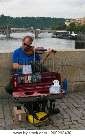 PRAGUE, CZECH REPUBLIC - AUGUST 16, 2017: Great performance of street musician of violinist on Charles Bridge, Prague old town