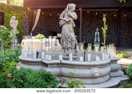 Fountain decorated with statues and candles. Wedding ceremony decoration details. Fountain with statues in outdoor restaurant