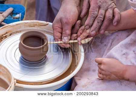 A child under the guidance of a master is engaged in the manufacture of a clay pot