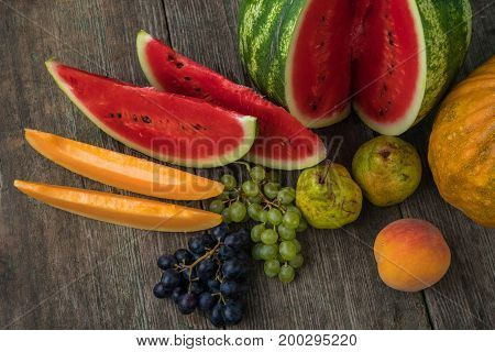 Watermelon, Melon, Grapes, Peach, Pear, Pumpkin On Old Wooden Table