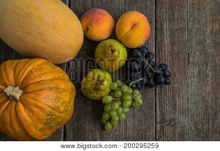 Melon, Grapes, Peach, Pear And Pumpkin On Old Wooden Table.