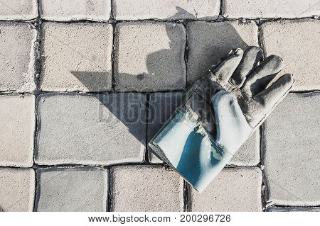 Old leather gloves leave on paving footpath background