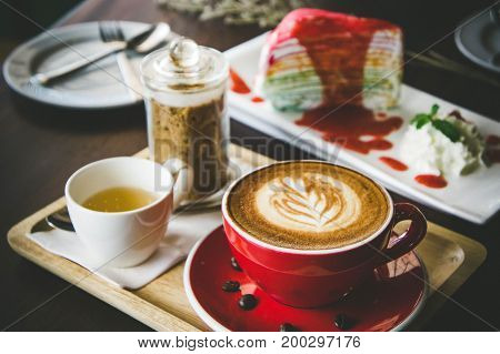 aroma coffee red cup latte art and tasty cake on wood table in coffee shop with vintage dark tone and copy space