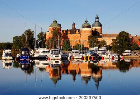 Mariefred Sweden - August 15 2017: The morning sun shines at Gripsholm Castle that reflects in the water next to the marina by pleasure boats.