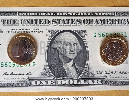 1 Pound And 1 Euro Coin, And One Dollar Note Over Metal Background