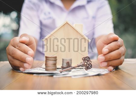 Hands boy holding little wood house and coins concept save money for my home selective and soft focus hipster tone