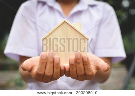 Hands boy holding little wood house selective and soft focus hipster tone