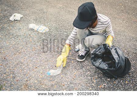 Girl hand in yellow gloves picking up empty of bottle plastic into bin bag volunteer concept