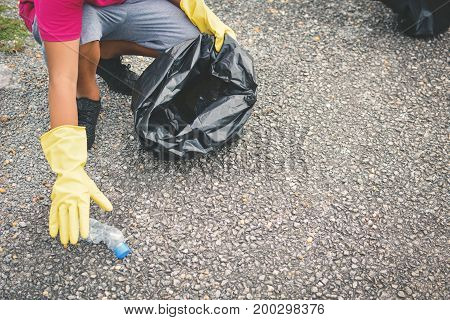 Boy hand in yellow gloves picking up empty of bottle plastic into bin bag volunteer concept