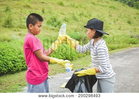 Children hands in yellow gloves picking up empty of bottle plastic into bin bag volunteer concept selective and soft focus