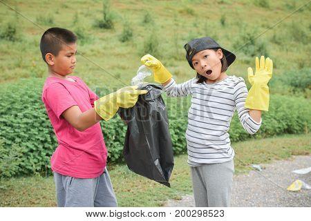 Children hands in yellow gloves picking up empty of bottle plastic into bin bag volunteer concept