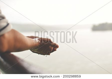 Close up girl hand during rain fall on park