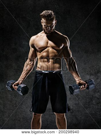 Young guy working out with dumbbells. Photo of strong male with naked torso on dark background. Strength and motivation.