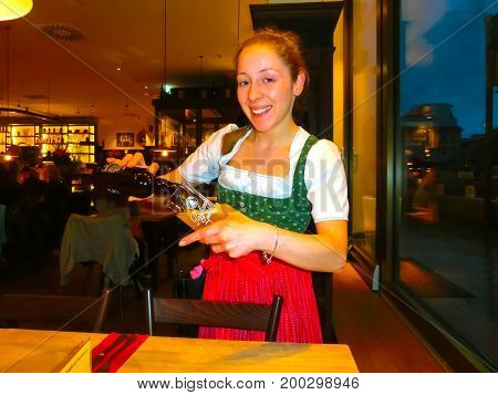 Munich, Germany - May 01, 2017: Young woman as queen in Traditional Bavarian Tracht in restaurant or pub Stubn with beer at Munich, Germany on May 01, 2017