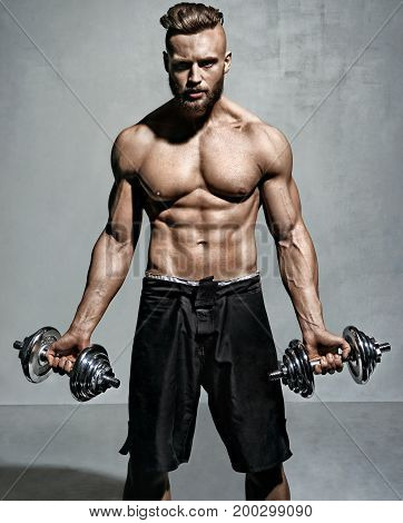 Sporty man doing exercise with dumbbells. Photo of muscular man on grey background. Strength and motivation.