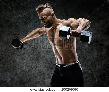 Bodybuilder doing the exercises with dumbbells. Photo of young man with naked torso on dark background. Strength and motivation.