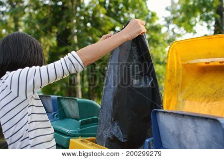 Girl holding empty bag into the trash