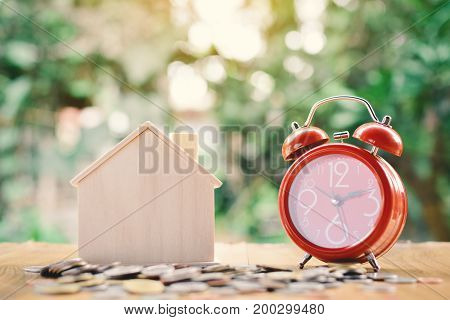Coins and wood house with red alarm clock on table tree bokeh background concept save money for home selective and soft focus vintage tone