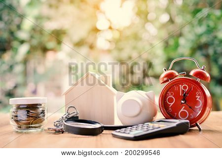 Coins and wood house with red alarm clock office equipment on table tree bokeh background selective and soft focus vintage tone