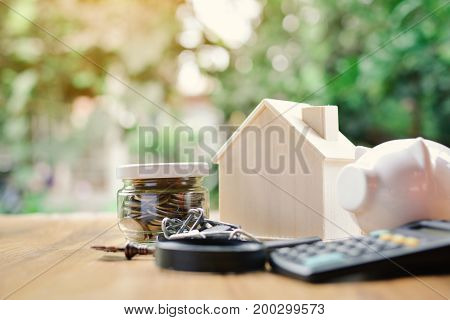 Coins and wood house with office equipment on table tree bokeh background selective and soft focus vintage tone