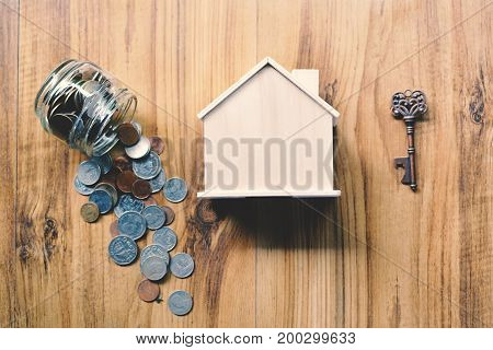 Coins and wood house on table concept save money for home selective and soft focus vintage tone