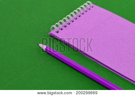 Top view of open spiral blank notebook with pencil on green paper background. Open vintage notebook. Empty notebook paper for text with  pencil . office concept top view.Copy space. Space for text.