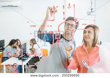 Mature tutor standing with young student near glass board and drawing scheme together.