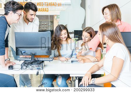 Young students sitting around desktop with computer and coworking with mature teacher and book.