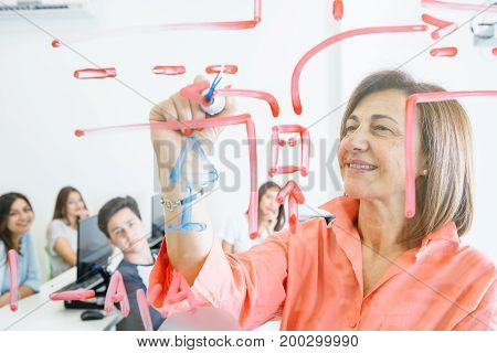 Mature woman drawing on glass board and working with young students in modern classroom.
