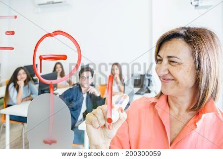 Mature cheerful woman drawing on glass board with marker showing new information for students.
