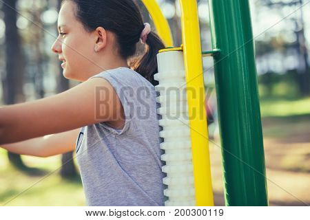 Young smiling teenage girl does exercises at massager simulator in park