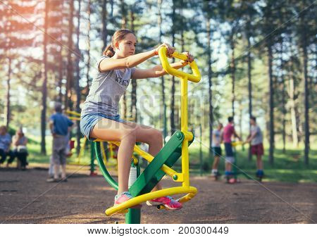 Young smiling teenage girl does exercises at simulator in park