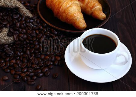 Hot black coffee and bean with two croissant for eating breakfast.
