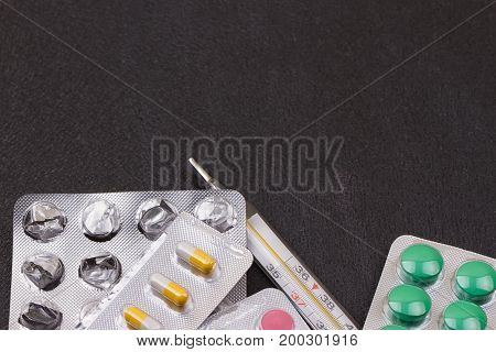 thermometer pink yellow green white pills on black background