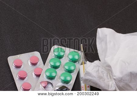 pills thermometer paper napkin and crumpled napkin on it. Top view medicine concept photo. Black background