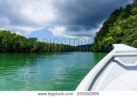 In boat shot during the river cruise showing the tree covered hills, cloudy skies and beautiful green water in in Kilim park Langkawi. This is a popular tourist destination