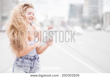 Photo of a woman with vintage music headphones around her neck surfing internet on a tablet pc and posing against urban city background.