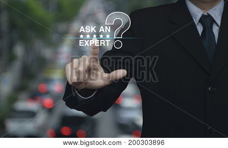 Businessman pressing ask an expert with star and question mark sign icon over blur of rush hour with cars and road