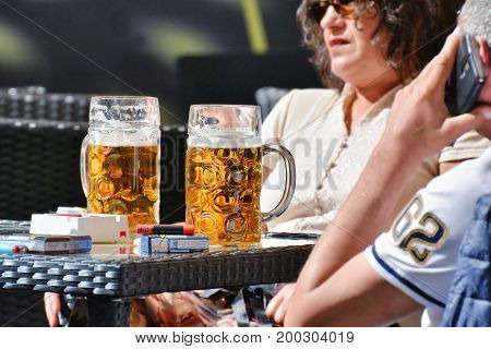 CLUJ-NAPOCA ROMANIA - MAY 27 2017: Two pints of beer on a table in front of a middle aged couple at a sidewalk cafe.