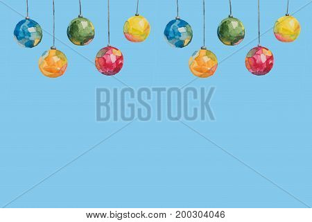 Several Christmas tree-colored multi-colored balls painted with watercolors hanging on threads on a blue background