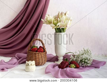 Still life with strawberries and varietal tulips on the table close-up