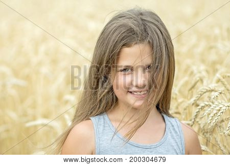 Head and shoulders portrait of adorable smiling little girl at a summer day with wheat field background