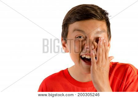 Young teenage boy isolated on white crying with laughter