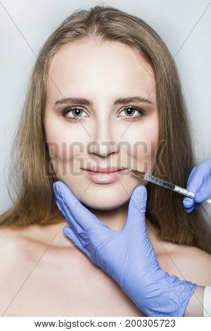 Doctor aesthetician in blue medical gloves makes hyaluronic acid beauty injections in lips to make correction and augmentation of the lips of young female patient