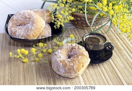 Cup with coffee, donuts and bouquet of mimosa on the table close-up