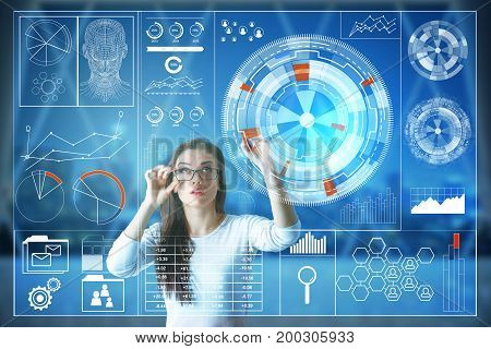 Thoughtful european woman using digital business screen in interior with night city view. Touchscreen and infograph concept. Double exposure