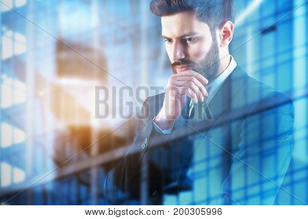 Thoughtful businessman on city glass building background. Employment concept. Double exposure