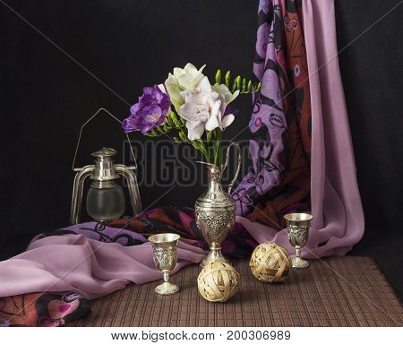 Still life with freesia and silver vase on a table close-up