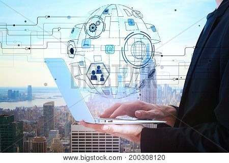 Side view of young businessman using laptop on city background with abstract business projection. Technology and interface concept. Double exposure