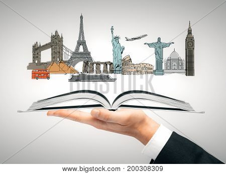Hand holding open book with travel sketch. Vacation concept. 3D Rendering
